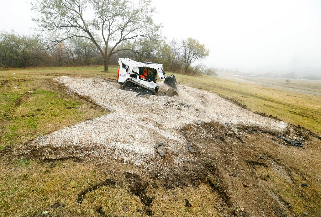 Texas Department of Transportation crews razed the imprint of an iconic Texas-shaped sign on a hillside median off Interstate 20 between Mountain Creek Parkway and Spur 408 in southwest Dallas on Dec. 13, 2016. The sign was being removed because of safety concerns, since visitors drive off road to get to the sign and had to merge back onto the interstate without an entrance ramp.