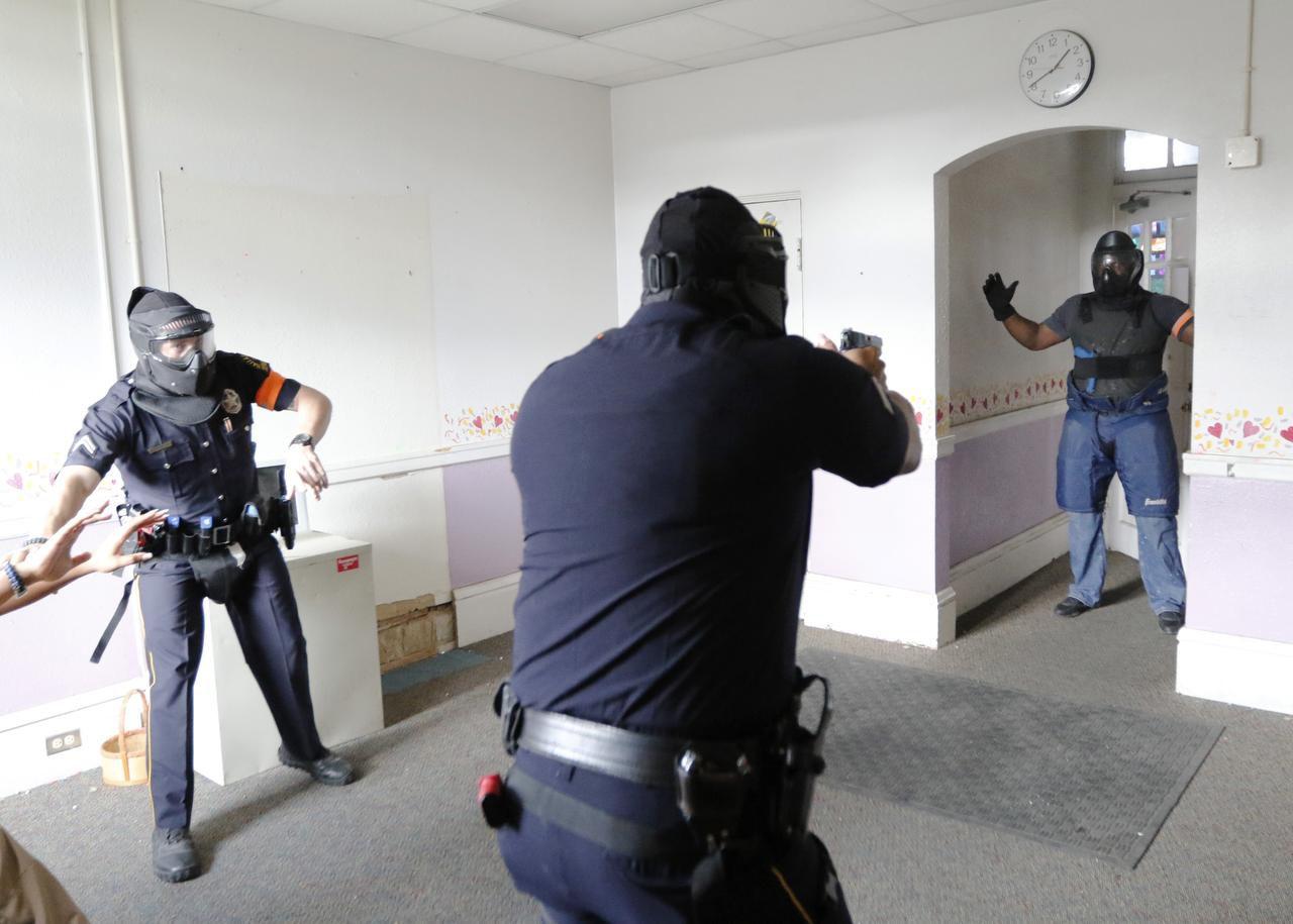 Los agentes de policía Daniel Elk (izq.) y Perry Strickland (centro) sacan sus armas durante un ejercicio de entrenamiento para reducir el uso de la fuerza letal. (DMN/DAVID WOO)