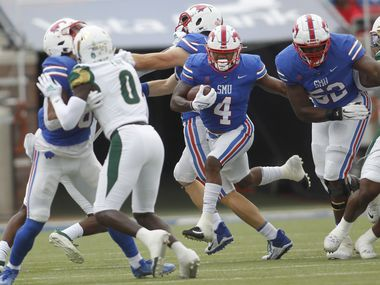 SMU running back Tre Siggers (4), center, bolts into the South Florida secondary for a first quarter first down. SMU defeated South Florida 41-17. The two teams played their NCAA football game at SMU's Ford Stadium in Dallas on October 2, 2021. (Steve Hamm/ Special Contributor)