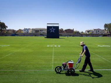 Groundskeepers stripe the field in preparation for opening of Dallas Cowboys training camp on Tuesday, July 20, 2021, in Oxnard, Calif.