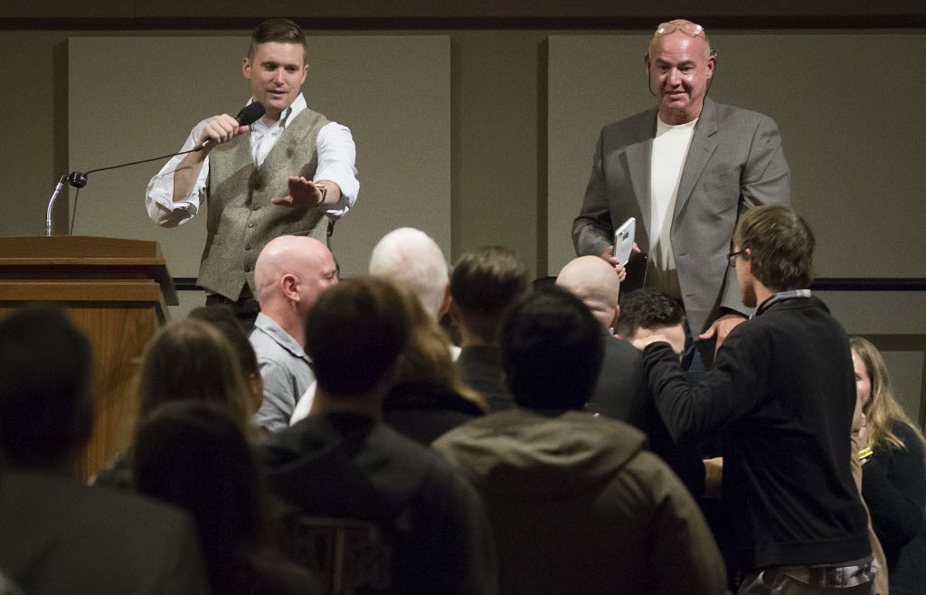 Richard Spencer motioned for calm as supporters and opponents scuffled in front of the stage while he spoke at the Memorial Student Center at Texas A&M University on Dec. 6, 2016.