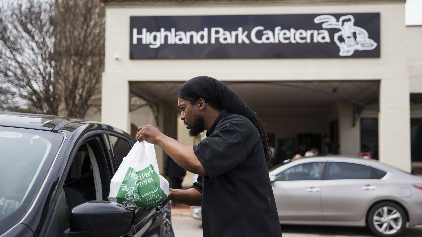 Executive Chef Johnny Howard delivers a meal to a driver outside Highland Park Cafeteria on Wednesday, March 18, 2020 in Dallas. Employees handed out free meals outside the restaurant after Dallas restaurants and bars were closed due to the spread of COVID-19.