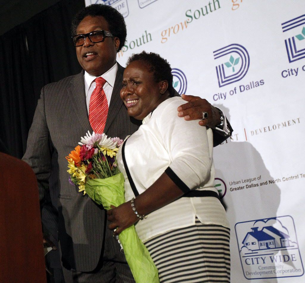 """Dwaine Caraway presented a bouquet of flowers to Carolyn Davis at the new Lancaster Urban Village in 2014, when both were Dallas City Council members. Caraway referred to Davis as """"his little fireball"""" and thanked her for her help on an apartment complex project."""