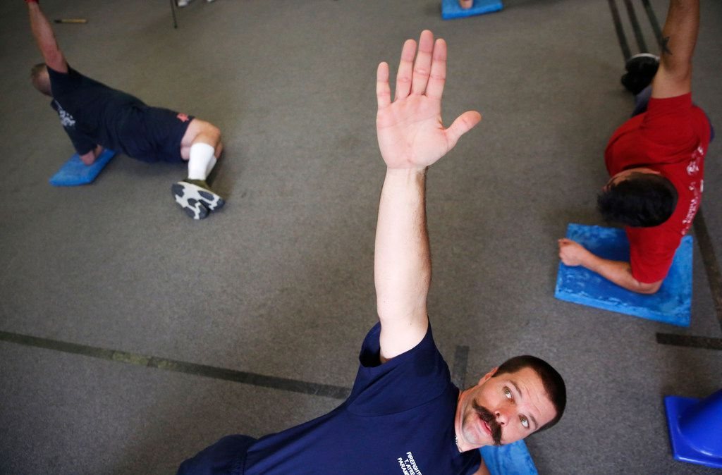 Addison firefighter/paramedic Troy Ayres holds a pose at REACT gym in Addison, Texas on Thursday, Jan. 24, 2019. The gym is now offering a free injury prevention training program to Addison first responders. (Rose Baca/Staff Photographer)