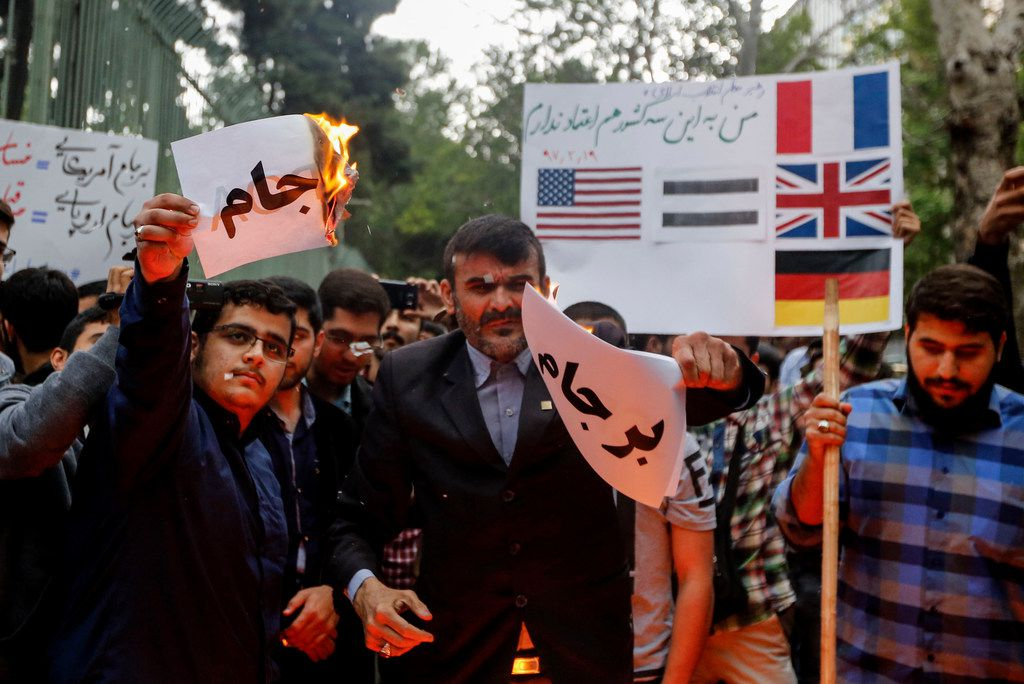 Iranians burn slogans during an anti-US demonstratin outside the former US embassy headquarters in the capital Tehran on May 9, 2018. / AFP PHOTO / ATTA KENAREATTA KENARE/AFP/Getty Images