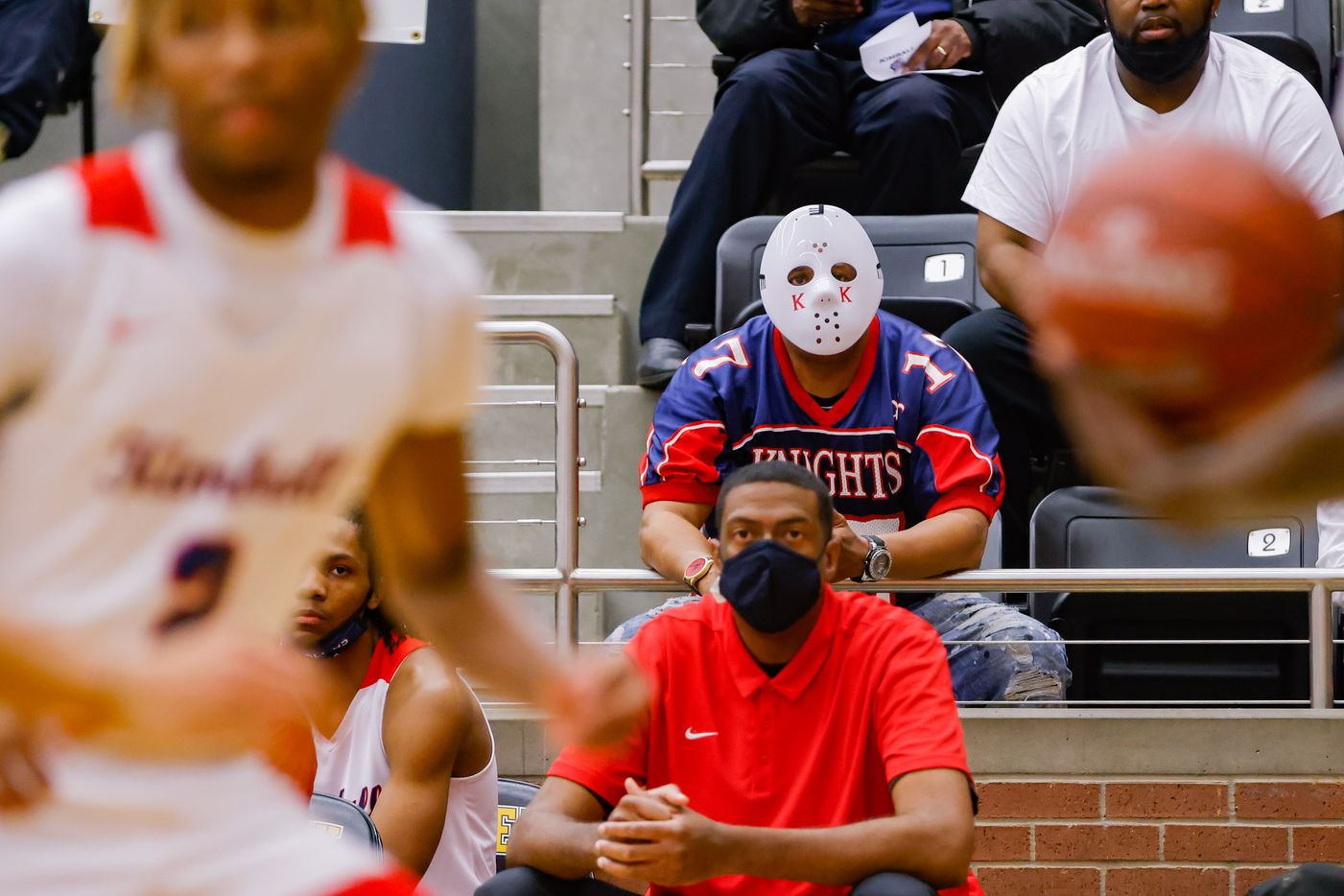 A Kimball fan wearing a goalie mask watches during the first half of a boys basketball UIL Class 5A Region II playoff game against Lancaster in Forney on Friday, March 5, 2021. (Juan Figueroa/ The Dallas Morning News)