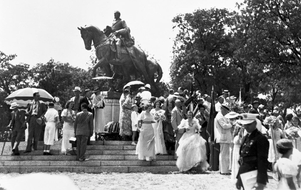 Dressed for a celebratory occasion, members of a crowd mill about the newly unveiled statue of Robert E. Lee after President Franklin D. Roosevelt dedicated it at Lee Park in Dallas, Texas, on June 12, 1936. Pres. Roosevelt also spoke at the Texas Centennial Exposition, at Fair Park, earlier in the day.