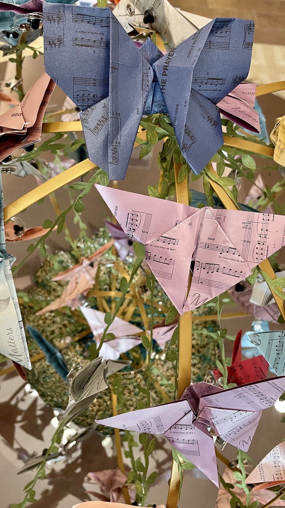 The life cycle of a Presbyterian Village North origami butterfly begins with a piece of sheet music.
