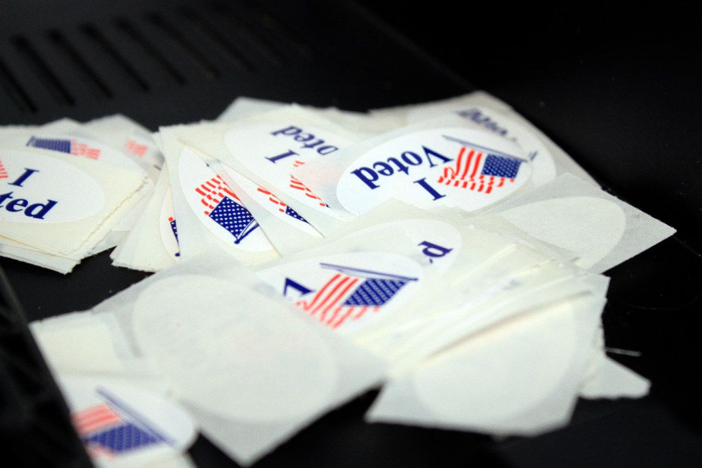 Voter stickers sit in a pile near a ballot machine at an early voting site.