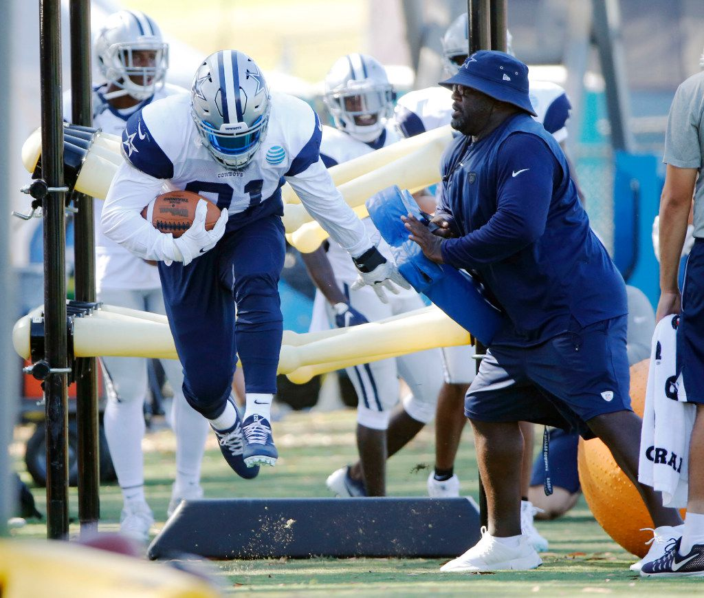 FILE - Dallas Cowboys running back Ezekiel Elliott (21) runs through a drill as running backs coach Gary Brown works with him in a drill during training camp in Oxnard, California on Monday, August 7, 2017. (Vernon Bryant/The Dallas Morning News)
