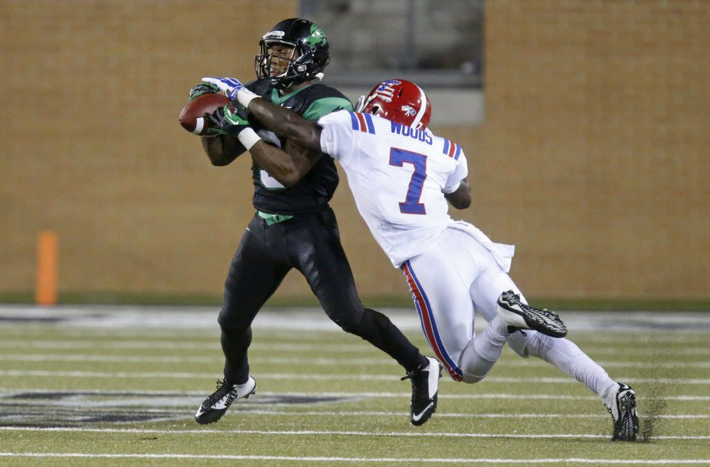 North Texas Mean Green wide receiver Carlos Harris (9) catches a pass in front of Louisiana Tech Bulldogs defensive back Xavier Woods (7) in the third quarter during the Louisiana Tech University Bulldogs vs. the University of North Texas Mean Green NCAA football game at Apogee Stadium in Denton on Thursday, September 11, 2014.  (Louis DeLuca/The Dallas Morning News
