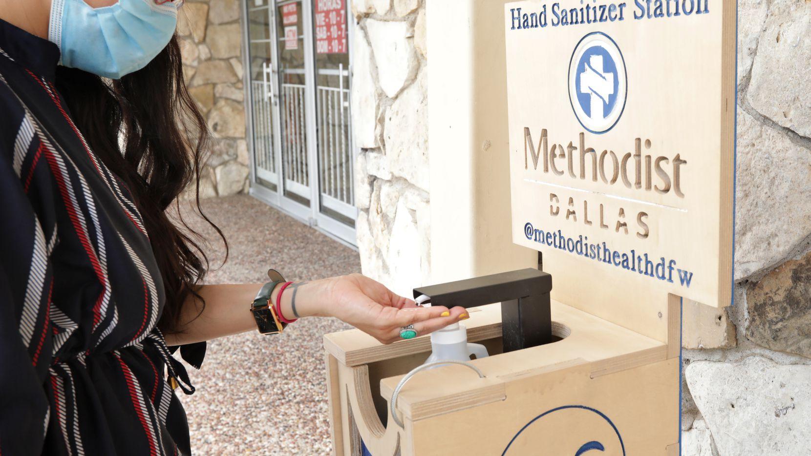 Leslie Cannon prueba una de las estaciones con gel antibacterial instaladas a lo largo del código postal 75211 el más afectado por el coronavirus.