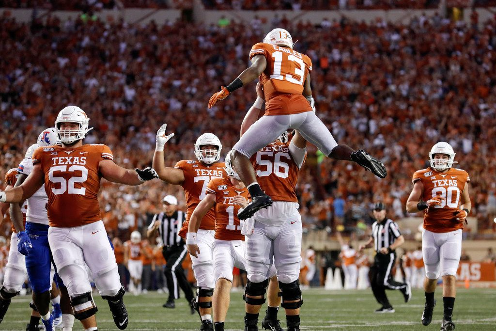 AUSTIN, TX - AUGUST 31:  Zach Shackelford #56 of the Texas Longhorns lifts Brennan Eagles #13 after a touchdown reception in the second quarter against the Louisiana Tech Bulldogs at Darrell K Royal-Texas Memorial Stadium on August 31, 2019 in Austin, Texas.  (Photo by Tim Warner/Getty Images)