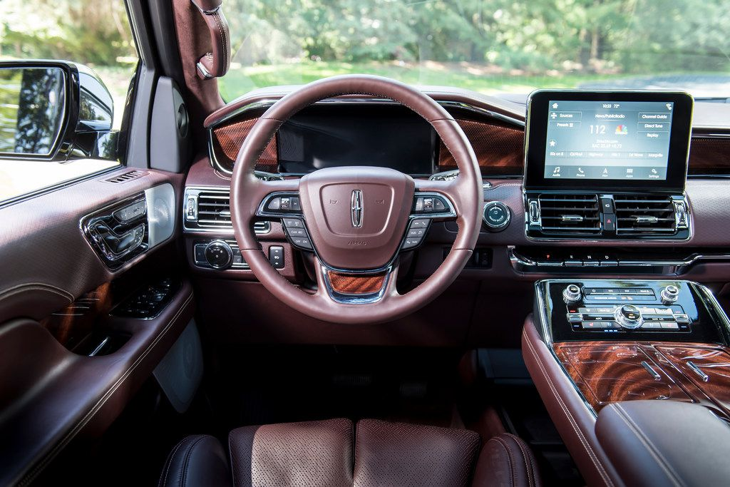 The Navigator has wood trim on the dash, doors and center console, and the console has open storage beneath for handbags.