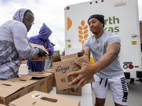 UNT-Dallas student Kevan Wise, right, and alum Darnell Davis unload boxes of food from a North Texas Food Bank truck on Tuesday in South Dallas. The boxes were loaded into the cars of those in need of food because of the coronavirus outbreak.