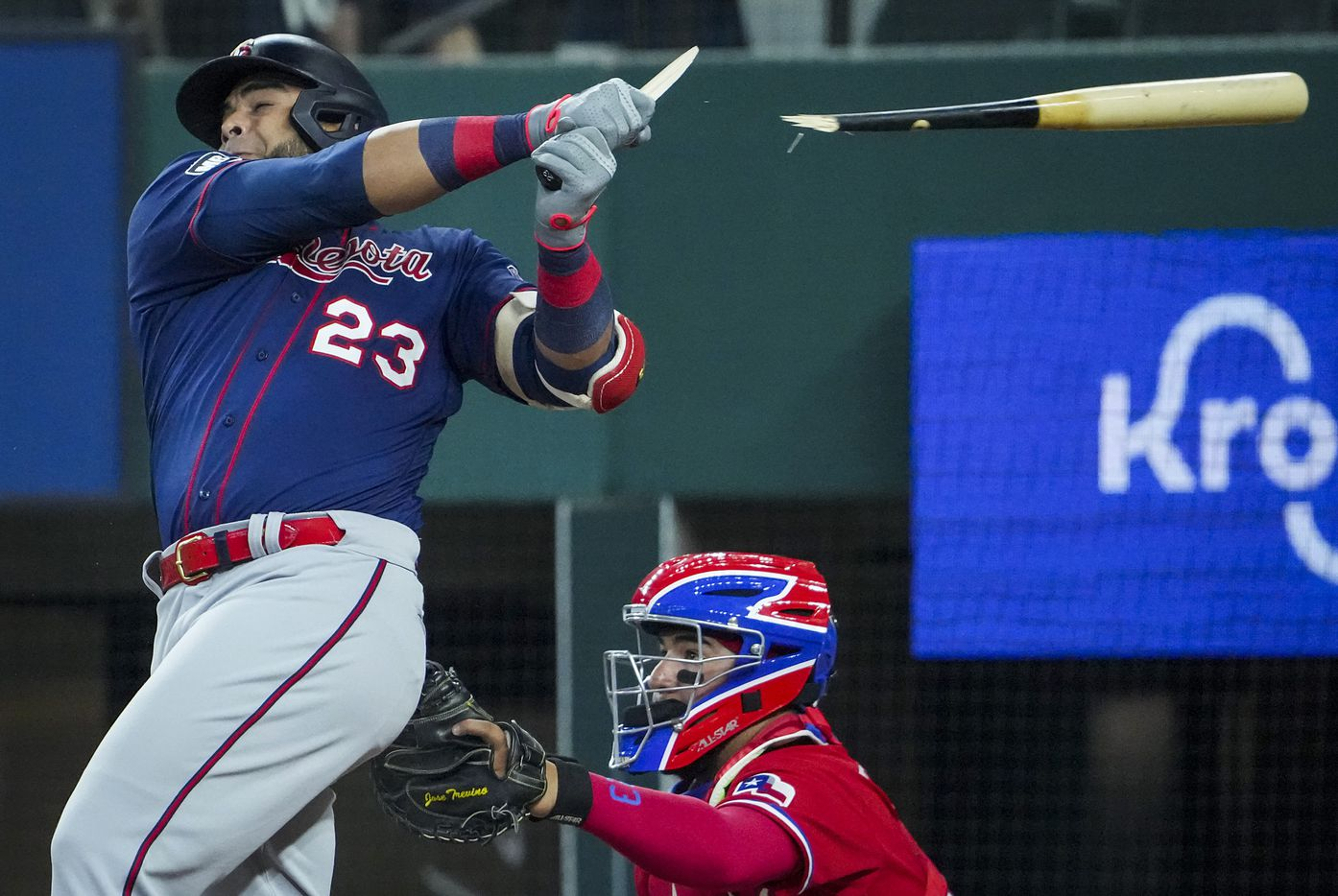Minnesota Twins designated hitter Nelson Cruz  breaks his bat on an RBI single as Texas Rangers catcher Jose Trevino works behind the plate during the first inning at Globe Life Field on Friday, June 18, 2021.