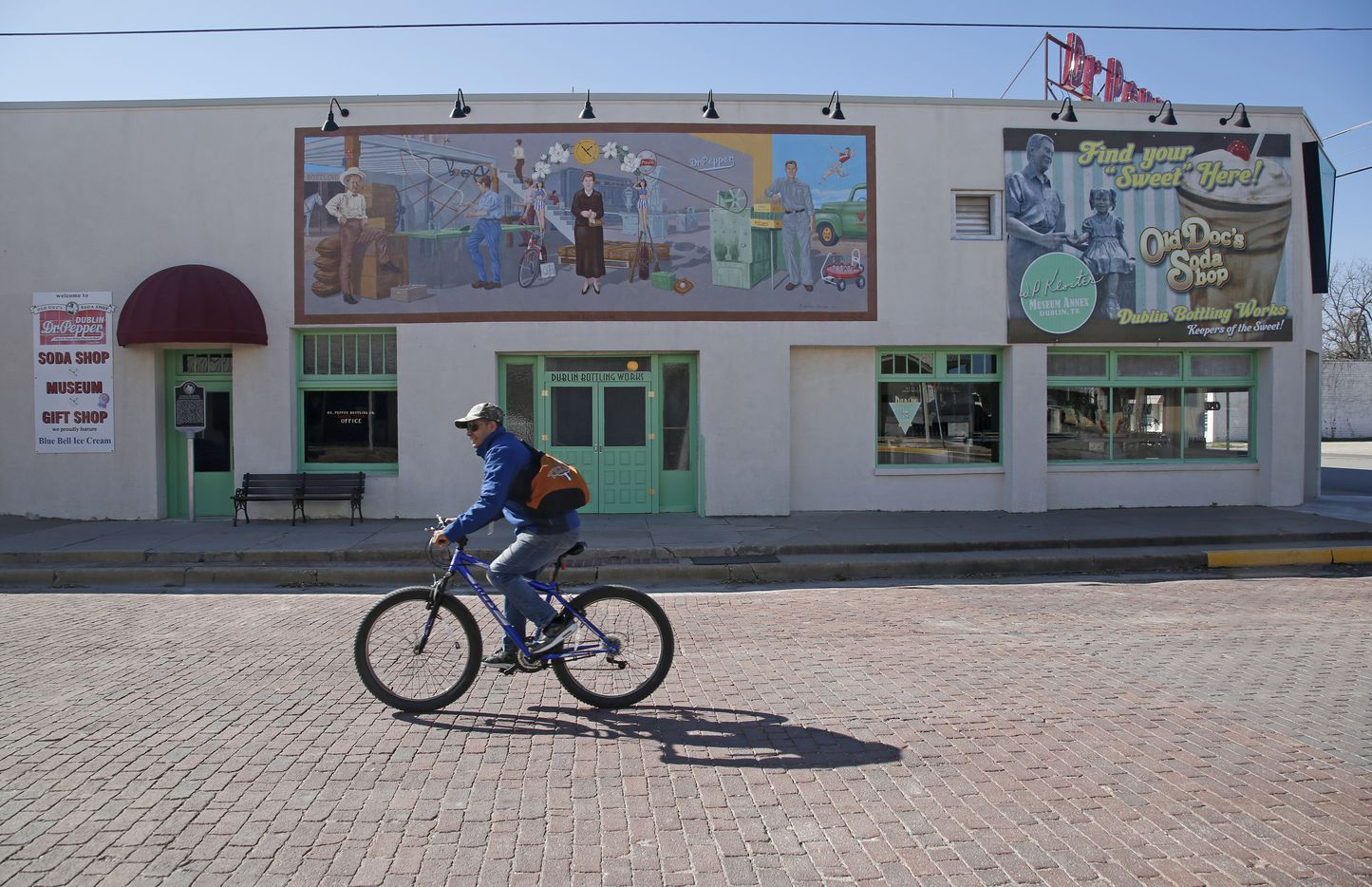 A cyclist passes in front of the Dublin Bottling Works, museum and soda shop in Dublin, Texas Friday Feb. 24, 2017. An old Dr Pepper sign is still on the roof even though it's no longer bottled there. (Guy Reynolds/The Dallas Morning News)
