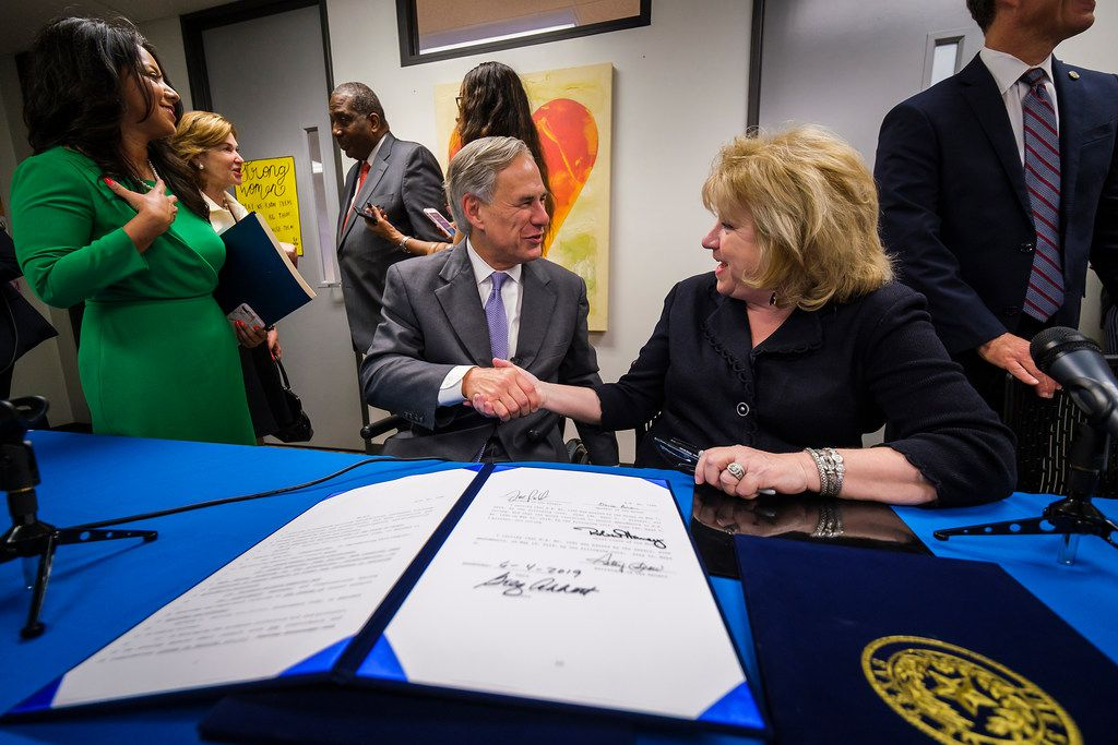 Governor Greg Abbott shakes hands with Sen. Jane Nelson as Rep. Victoria Neave (far left) looks on following a bill signing ceremony at New Friends New Life on Tuesday, June 4, 2019, in Dallas.  The Governor signed legislation related to human trafficking and the elimination of the rape kit backlog.