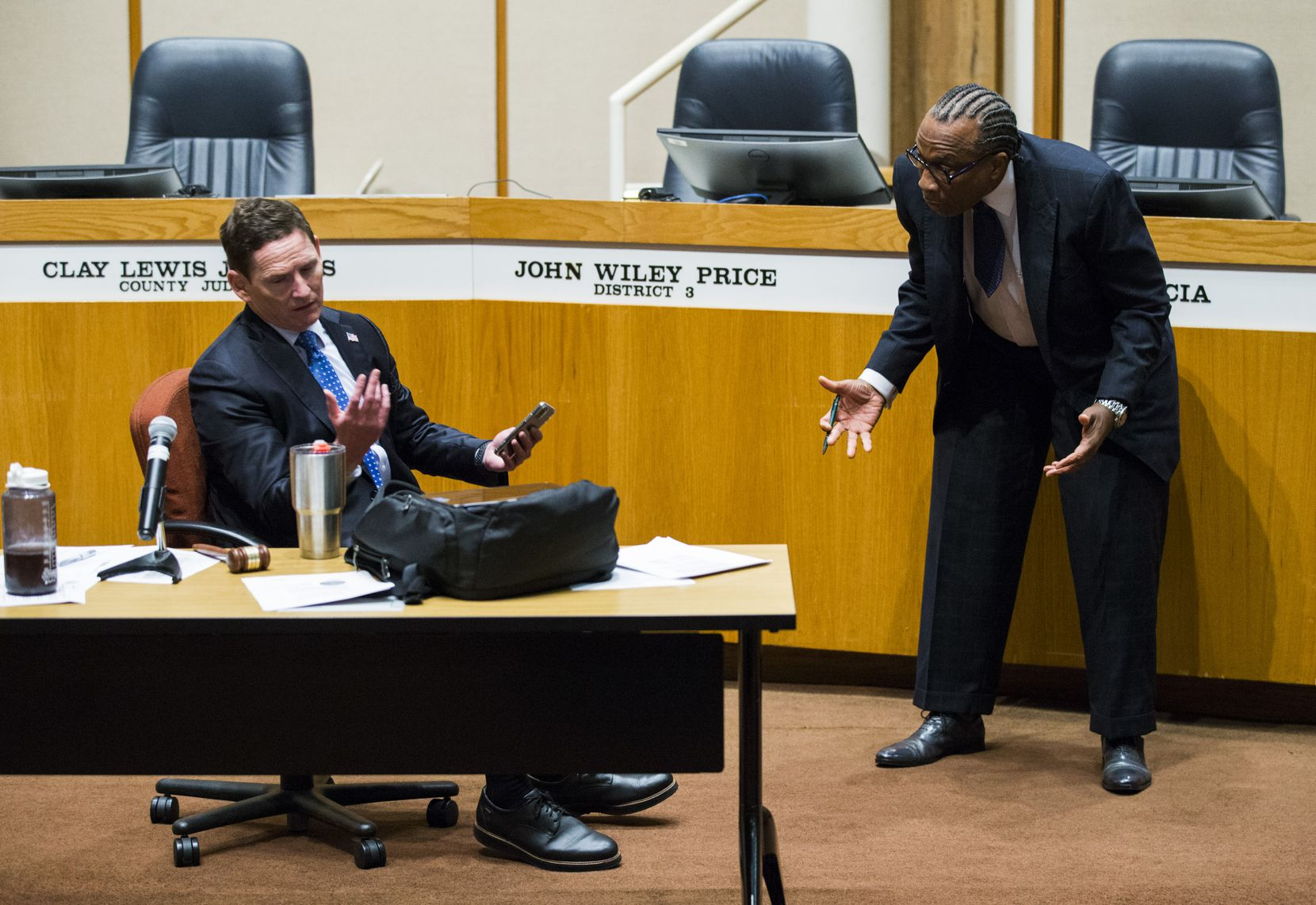 County Judge Clay Jenkins (left) and Commissioner John Wiley Price spar as the Dallas County Commissioners Court meets to discuss extending the local order on banning groups and closing restaurants.