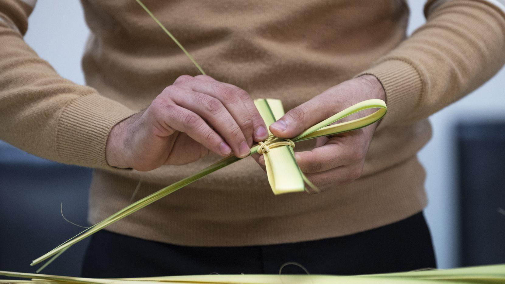 Junio García, voluntario de la iglesia San Juan Diego, fabrica una cruz con hoja de palma, como parte de un ritual previo al Domingo de Ramos, que marca el inicio de la Semana Santa en la fe católica.