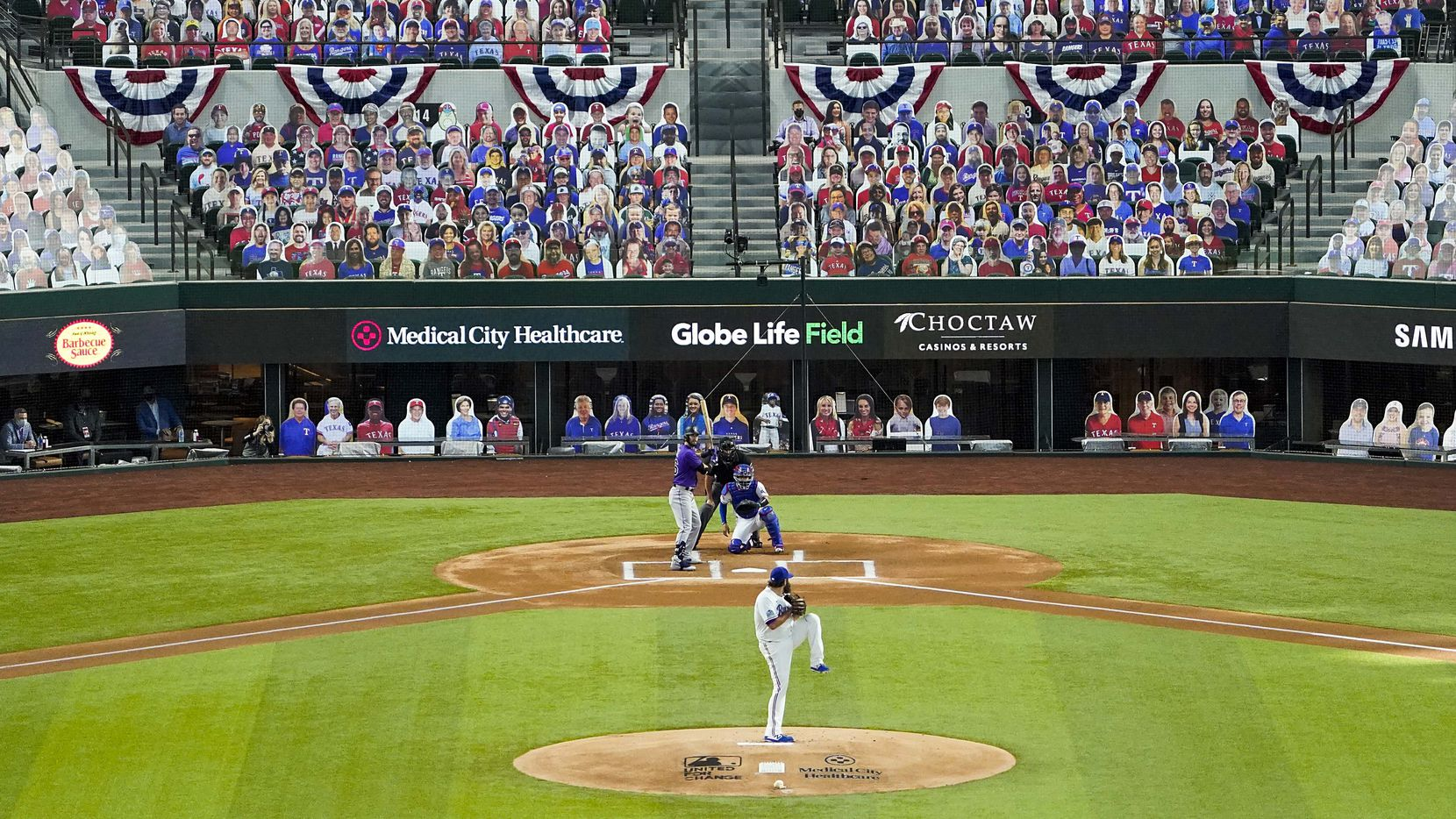 In front of a sea of cutout photos filling the empty seats, Texas Rangers pitcher Lance Lynn delivers a called strike to Colorado Rockies center fielder David Dahl for the first pitch in the history of the new stadium on opening day at Globe Life Field on Friday, July 24, 2020.