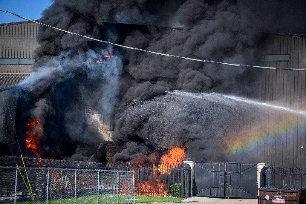 A fire truck sprayed water as flames erupted from a hangar at  Addison Airport on Sunday morning. All 10 people aboard a small plane died when it crashed into a hangar on takeoff, authorities said.