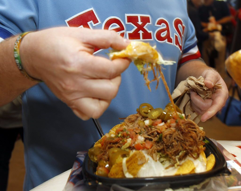 Troy Lestina eats the Grande Nachos at Globe Life Park in Arlington.