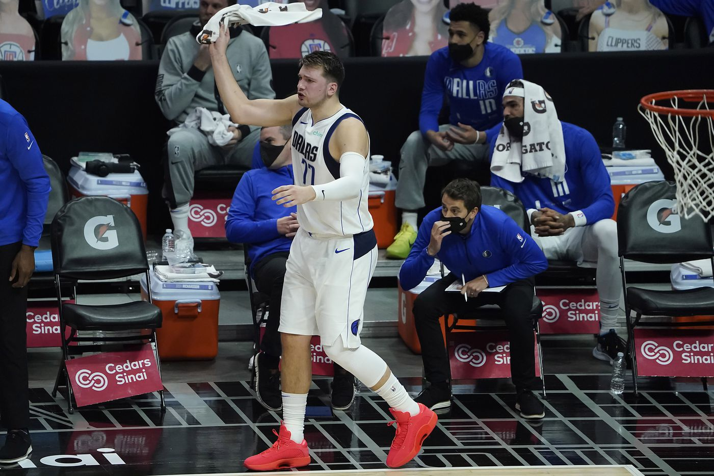 Dallas Mavericks guard Luka Doncic (77) cheers from the bench during the first half of an NBA playoff basketball game against the LA Clippers at Staples Center on Tuesday, May 25, 2021, in Los Angeles.