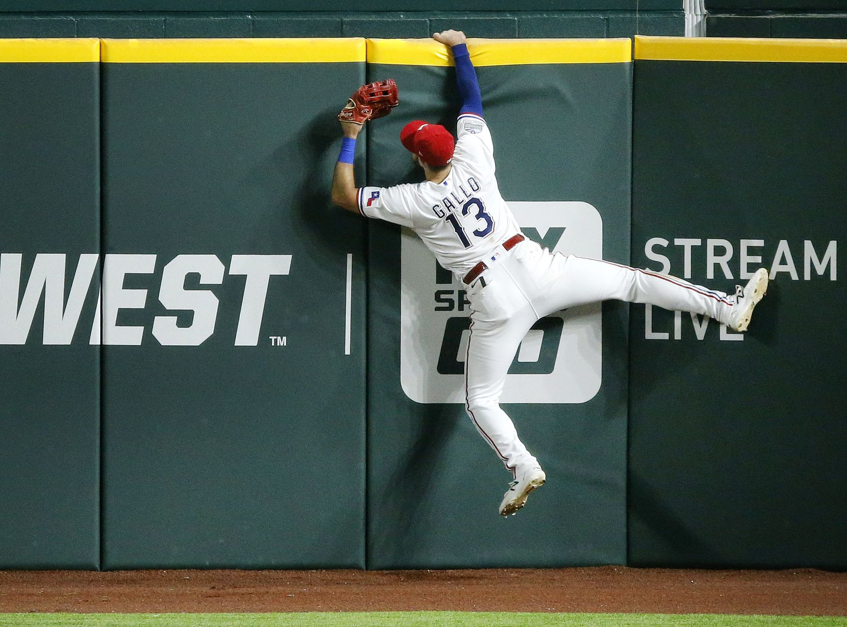Texas Rangers right fielder Joey Gallo (13) hangs on the wall after attempting to catch Seattle Mariners batter Kyle Seager's grand slam home run in the sixth inning at Globe Life Field in Arlington, Monday, August 10, 2020. (Tom Fox/The Dallas Morning News)