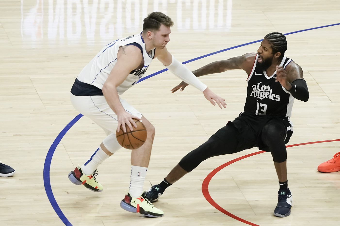 Dallas Mavericks guard Luka Doncic (77) is called for an offensive foul as LA Clippers guard Paul George (13) is knocked to the floor during the first half of an NBA basketball game at Staples Center on Saturday, May 22, 2021, in Los Angeles.