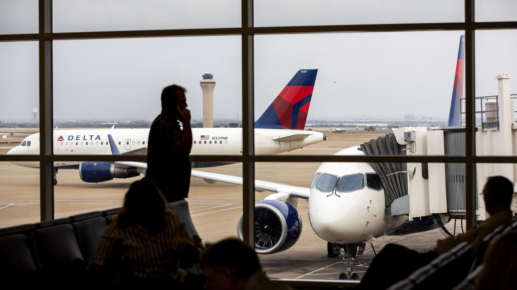 Delta's new Airbus A220-100 airplane sits parked at gate E15 of Terminal E at DFW Airport (right) as Delta Airbus A319 pushes back from the adjacent gate on Wednesday, Feb. 6, 2019. Beginning Thursday, Delta will put the twin-engine, narrow-body plane into service, with a 7:05 a.m. departure from DFW to New York's LaGuardia Airport. (Smiley N. Pool/The Dallas Morning News)