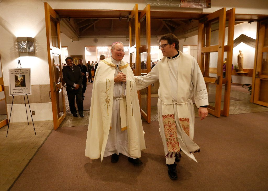 Bishop Edward Burns (left) and Rev. Joshua Whitfield walk out of the sanctuary after the Advent Holy Hour mass at Saint Rita Catholic Community in Dallas in December 2016.