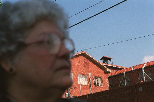 In this photo from August 1999, Lois Robison stands in front of the 'Walls Unit'  while talking with the media after finding out about her son's stay of execution in Huntsville.  Underneath the bell tower and cross is where the death chamber is located.