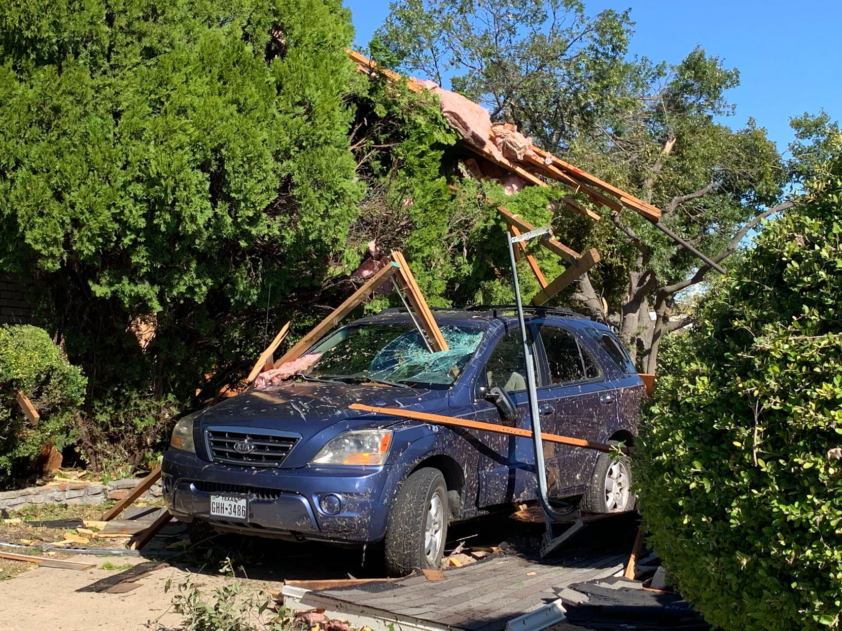 Debris from a nearby house dangles from a tree over a blue Kia SUV in the 1100 block of South Bowser Road in Richardson on Monday, October 21, 2019. Some of the wood crashed through the windshield. The neighborhood suffered extensive damage in Sunday night's tornado.
