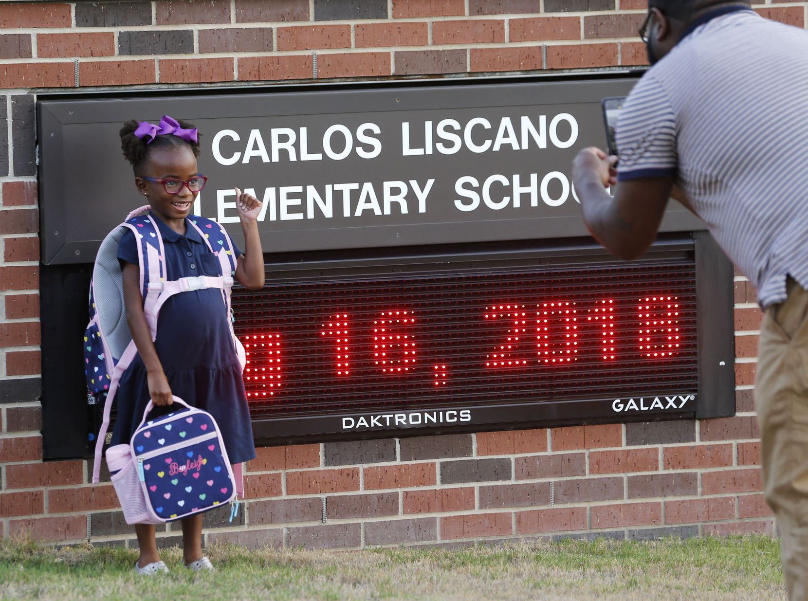 Kindergartner Bayleigh Briggs gets her photo taken by her dad, Chris Briggs, in front of the school sign on the first day of school at Carlos Liscano Elementary School in Frisco on Aug. 16, 2018.