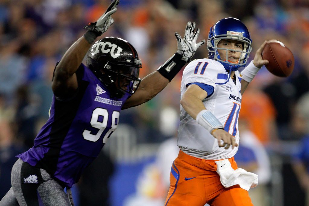 Kellen Moore #11 of the Boise State Broncos passes the ball as he is hit by Jerry Hughes #98 of the TCU Horned Frogs during the Tostitos Fiesta Bowl on January 4, 2010 in Glendale, Arizona.
