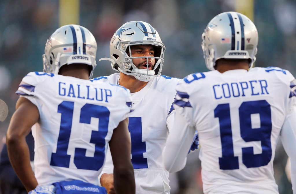 FILE - Cowboys quarterback Dak Prescott (4) talks with wide receivers Michael Gallup (13) and Amari Cooper (19) during warmups before a game against the Eagles at Lincoln Financial Field in Philadelphia on Sunday, Dec. 22, 2019.