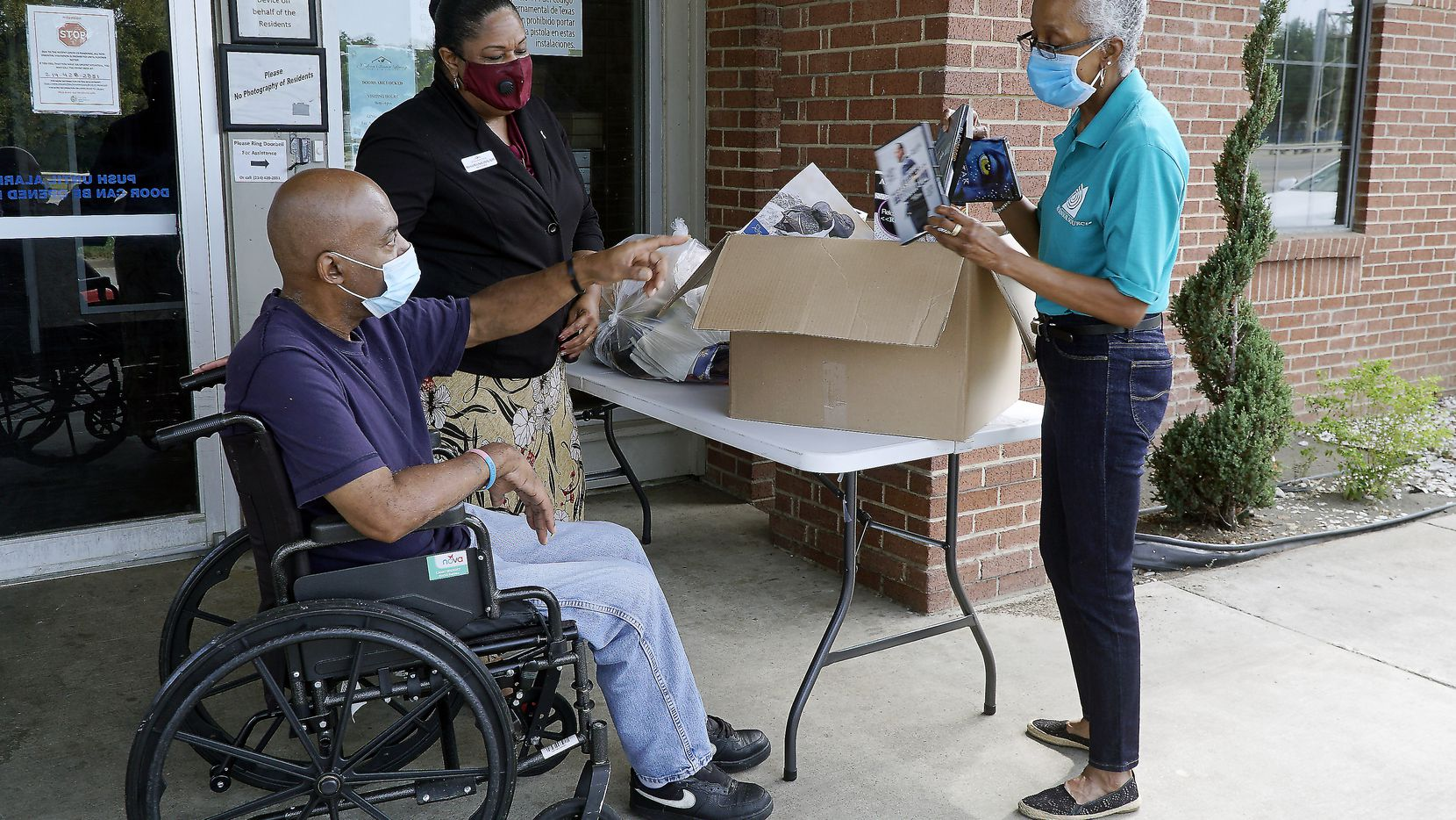 Friendly Visitor Coordinator Marsha Evans (right) delivers donations to Modern Senior Living resident Willie Wilson and Administrator Monté Mitchell in Dallas on Aug. 14, 2020.  (Lawrence Jenkins/Special Contributor)