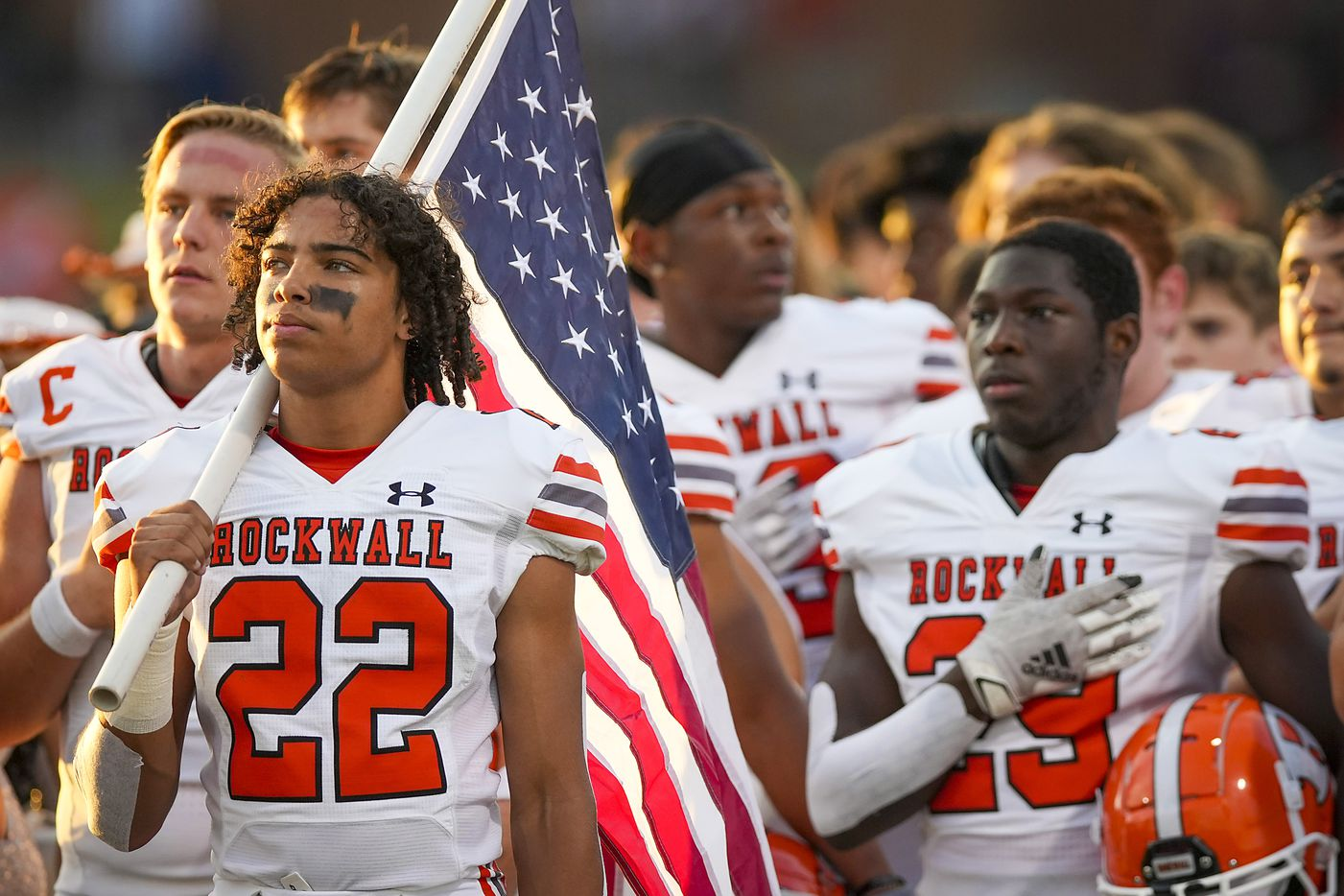 Rockwall running back  Parker Williams (22) holds the American flag as the team stands for the national anthem before a District 10-6A high school football game against Rockwall-Heath at Wilkerson-Sanders Stadium on Friday, Sept. 24, 2021, in Rockwall.