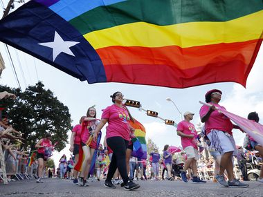 People marching with the Mobilize for Equality group pass by the Texas rainbow flag during the Texas Freedom Parade, Sunday, September 17, 2017. (Tom Fox/The Dallas Morning News)