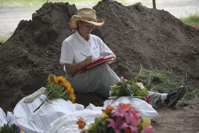Forensic anthropologist Lori Baker from Baylor University is a finalist for 2014 Dallas Morning News Texan of the Year. This file photo shows her working to exhume the remains of unidentified immigrants from a cemetery last year in Falfurrias, Texas.