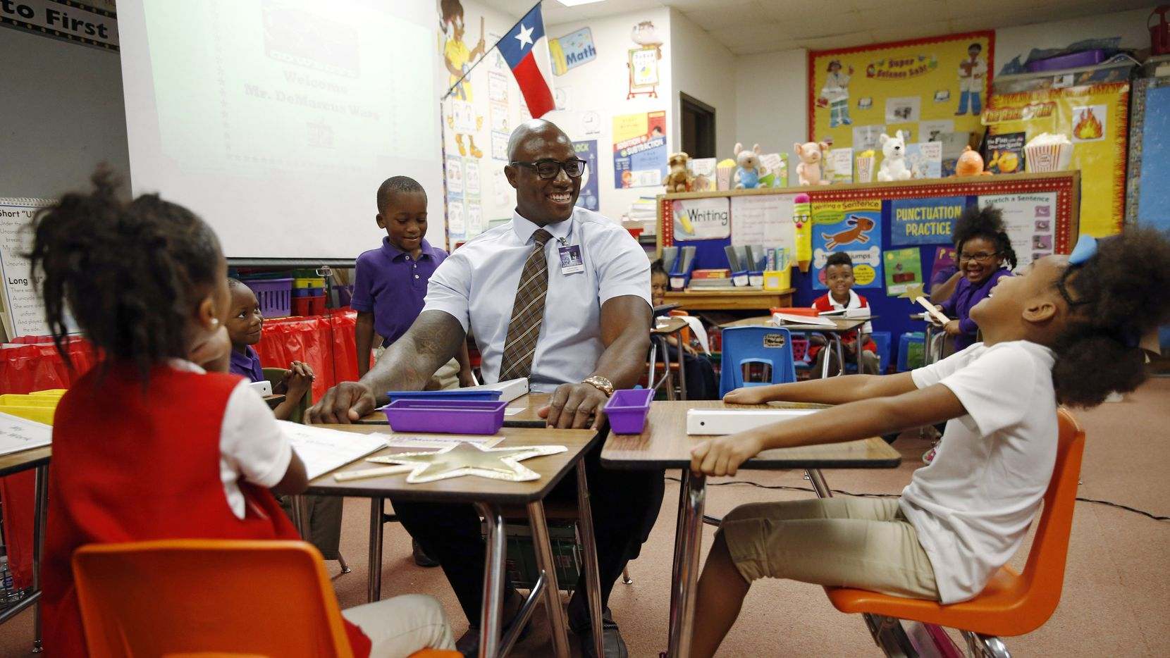 Former Dallas Cowboys player DeMarcus Ware squeezes into the desk belonging to Dewaylin Daniels' (standing to Ware's right) as Marley Dugas (left, seated in red) and Kaylen Tyson (right) share a laugh in a first-grade classroom at J.P. Starks Math, Science and Technology Elementary Vanguard.