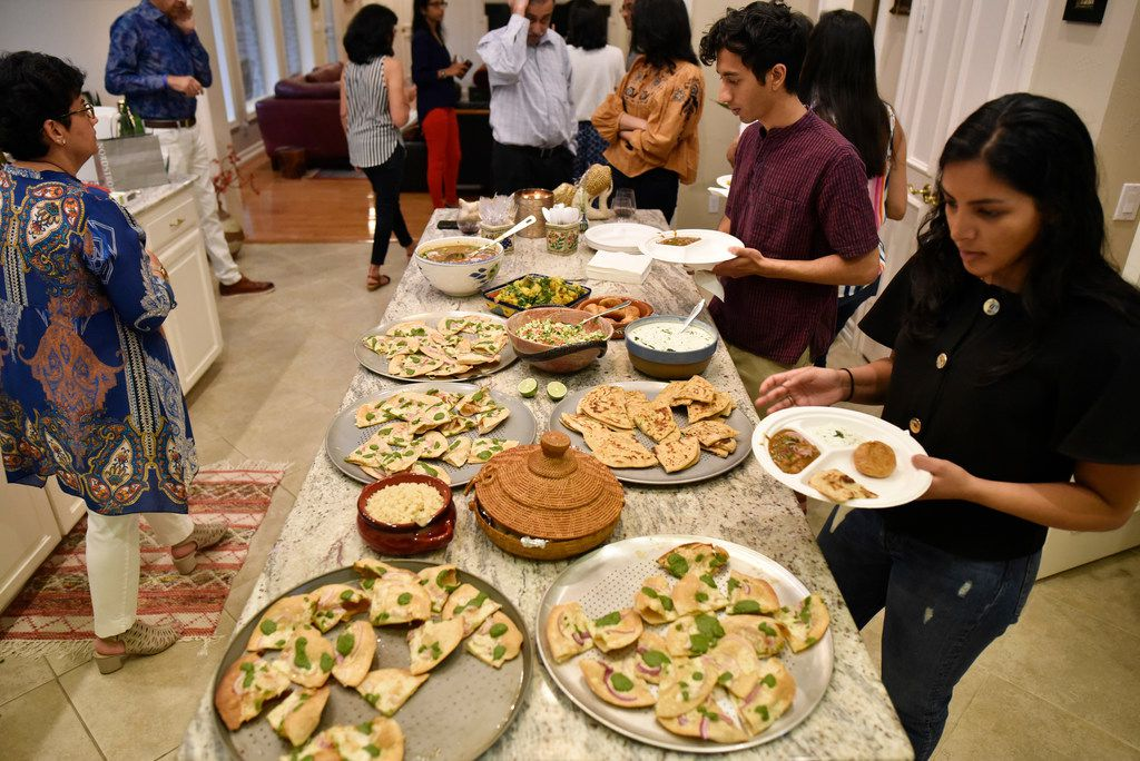Isha Elhence, right, and Hirsh Elhence, top-right, load their plates with food during a family dinner at Priya Krishna's family home in Dallas.
