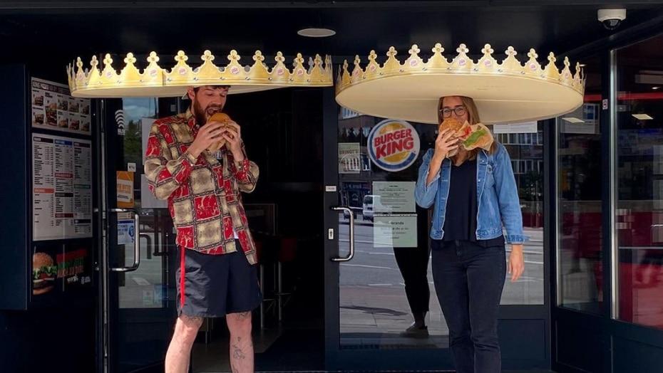Imagen de Burger King donde se ve a dos personas comiendo hamburguesas y portando sus 'coronas para la distancia social'.