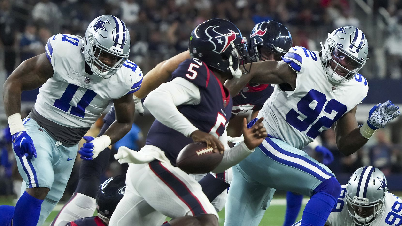 Houston Texans quarterback Tyrod Taylor (5) is flushed from the pocket by Dallas Cowboys linebacker Micah Parsons (11) and defensive end Dorance Armstrong (92) during the first half of a preseason NFL football game at AT&T Stadium on Saturday, Aug. 21, 2021, in Arlington.