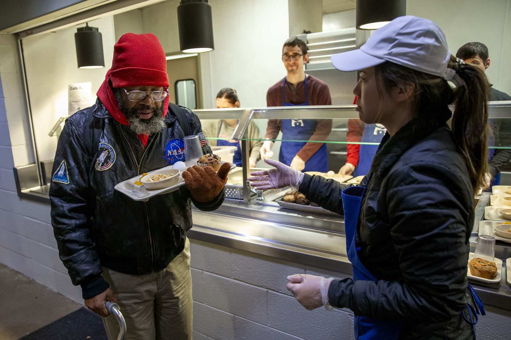 Nghiem Duong helped Randy as he carefully balanced his breakfast tray at The Bridge Homeless Recovery Center on Jan. 11, 2020.
