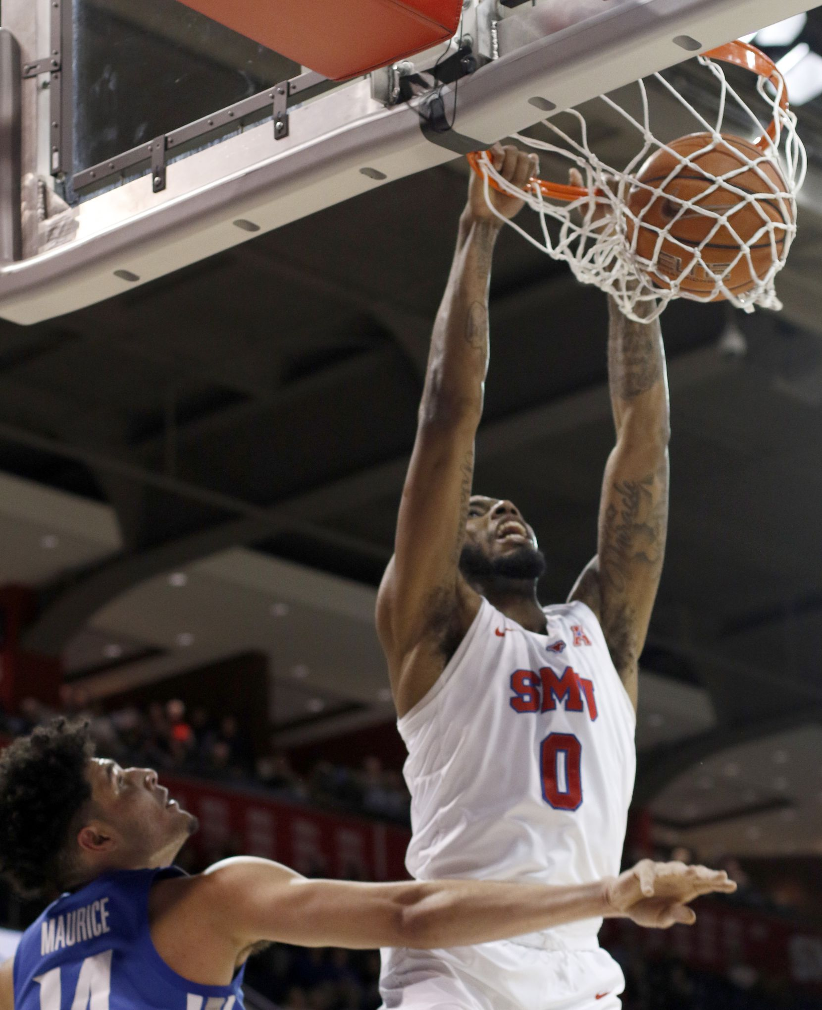 SMU guard Tyson Jolly (0) dunks over the defense of Memphis forward Isaiah Maurice (14) during first half action. The two teams from the NCAA's American Athletic Conference played their men's basketball game at SMU's Moody Coliseum in Dallas on February 25, 2020.