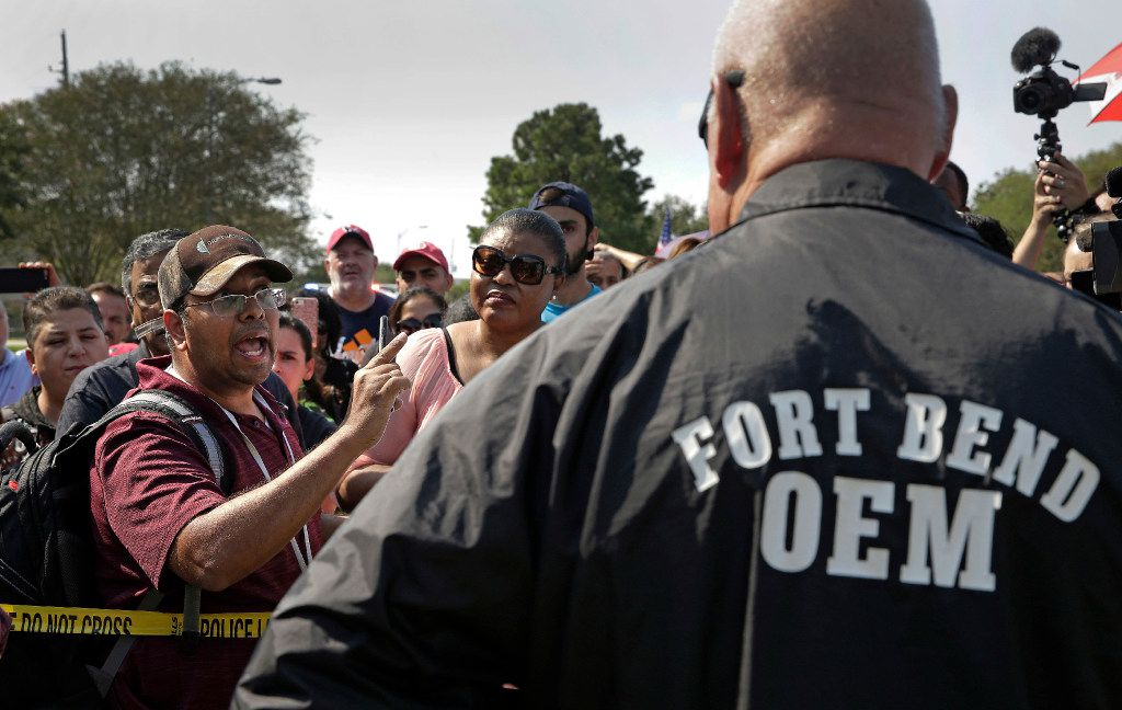 Residents question Fort Bend County Judge Bob Hebert at a roadblock into their Canyon Gate neighborhood which was flooded when the Barker Reservoir reached capacity in the aftermath of Harvey Saturday, Sept. 2, 2017, in Katy, Texas. Residents gathered at the checkpoint to vent their frustrations about not being able to get back into their homes which will remain flooded for several more days while the reservoir drains. (AP Photo/Charlie Riedel)