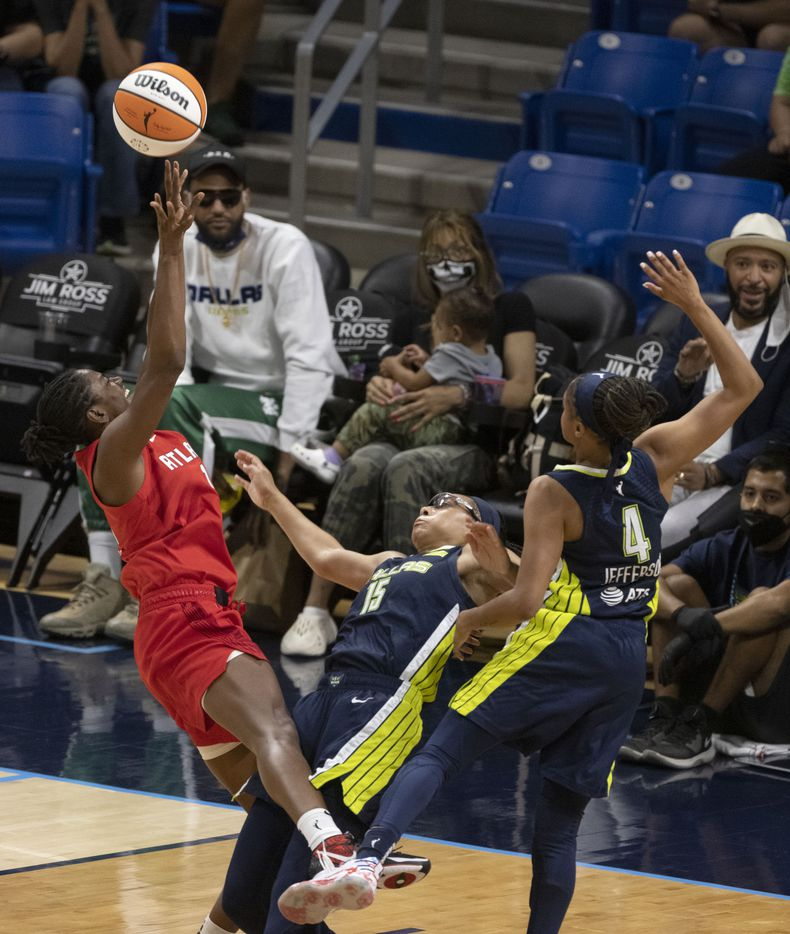 Atlanta Dream guard Tiffany Hayes (15) is called for an offensive foul as Dallas Wings guards Allisha Gray (15) and Moriah Jefferson (4) defend her during the second half of their WNBA basketball game in Arlington, Texas on Sept. 2, 2021. Dallas won 72-68. (Michael Ainsworth/Special Contributor)