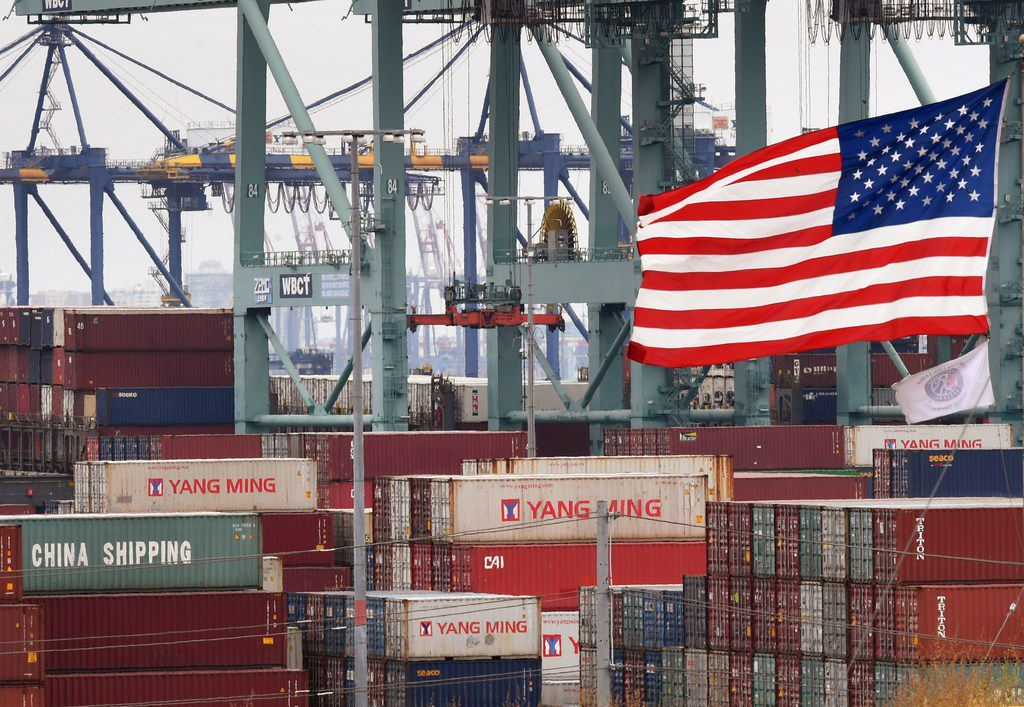 Chinese shipping containers are stored beside a U.S. flag after being unloaded at the Port of Los Angeles in Long Beach, Calif.